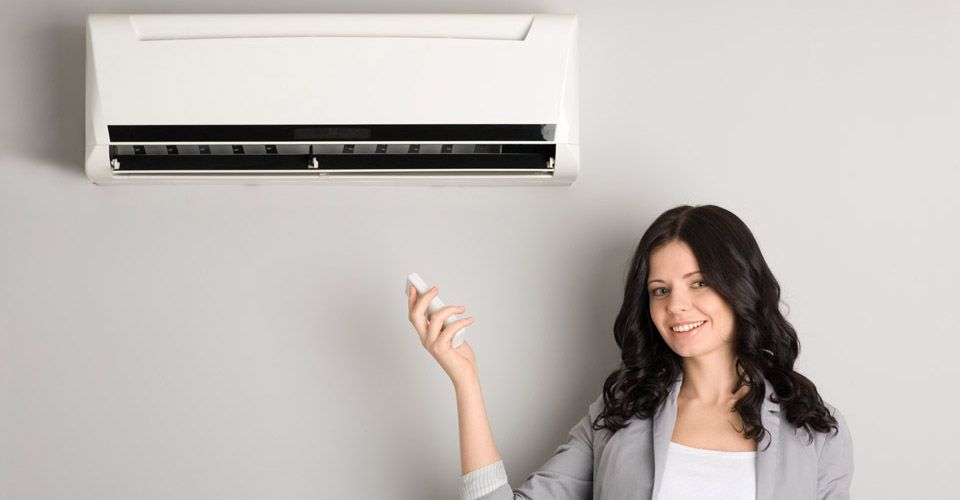 woman with remote control heating & air conditioning unit